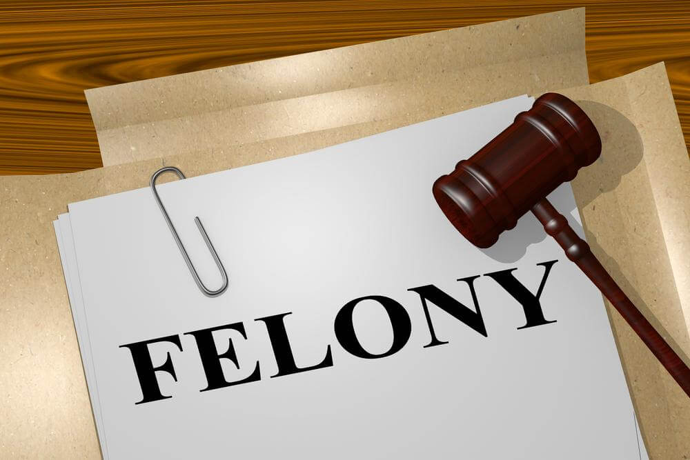 Gavel sitting on top of a stack of papers labeled felony